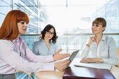 Коммерсантки обсуждая над ПК таблицы на таблице в офисе Стоковая Фотография RF