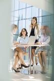 Коммерсантки обсуждая на таблице в офисе Стоковое Фото