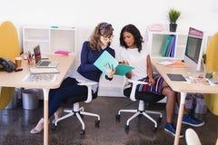 Коммерсантки обсуждая пока работающ в офисе Стоковое фото RF