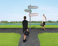 2 коммерсантки приближают к дорожному знаку Стоковые Изображения