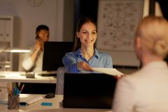 Коммерсантки при бумаги работая поздно на офисе Стоковая Фотография RF