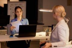 Коммерсантки при бумаги работая поздно на офисе Стоковое Изображение RF