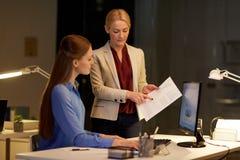 Коммерсантки при компьютер работая поздно на офисе Стоковая Фотография RF