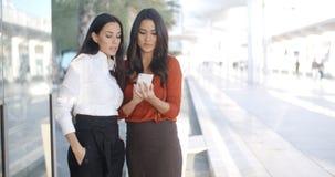 2 коммерсантки проверяя телефонное сообщение Стоковые Изображения