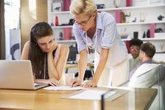 2 коммерсантки работая на компьтер-книжке в занятом офисе Стоковая Фотография RF