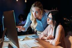 Коммерсантки работая на компьютере пока обсуждающ новый проект совместно Стоковая Фотография RF