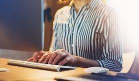 Коммерсантки работая на офисе с компьютером на ноче, молодым менеджером монитора битника печатая на клавиатуре, женских руках отп Стоковые Фото