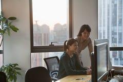 2 коммерсантки работая совместно в офисе на компьютере Стоковые Изображения