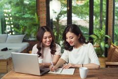 2 коммерсантки работая совместно Девушка сидит на таблице внутри Стоковые Изображения