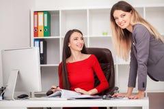 2 коммерсантки работая совместно Девушка сидит на таблице в f Стоковая Фотография