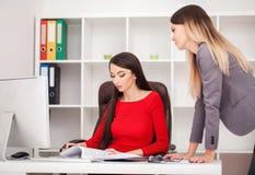 2 коммерсантки работая совместно Девушка сидит на таблице в f Стоковые Изображения RF