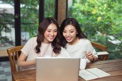 2 коммерсантки работая совместно Девушка сидит на таблице внутри Стоковое фото RF