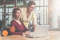 2 коммерсантки работая совместно На столе компьтер-книжка Женщина стоящая близко таблица, девушка сидит рядом с ей Стоковое Изображение