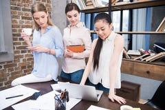 Коммерсантки работая с компьтер-книжкой и цифровой таблеткой на рабочем месте в современном офисе Стоковая Фотография