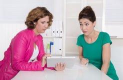 2 коммерсантки работая с таблетк-ПК на офисе. Стоковое Фото