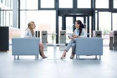 Коммерсантки сидя в кресле и имея переговор Стоковое фото RF