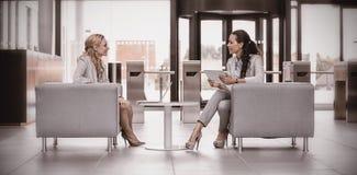 Коммерсантки сидя в кресле и имея переговор Стоковые Фото