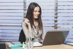 Коммерсантки сидя на ее столе в ручке удерживания офиса Стоковые Фото