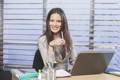 Коммерсантки сидя на ее столе в ручке удерживания офиса Стоковые Изображения