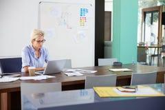 2 коммерсантки сидя на столах в офисе используя компьтер-книжки Стоковое фото RF