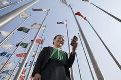 Коммерсантки смотря мобильный телефон с флагами в предпосылке. Стоковые Изображения RF