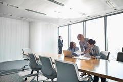 Коммерсантки смотря документы в встрече конференции Стоковое Изображение