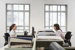 Коммерсантки смотря один другого пока сидящ в офисе Стоковые Фотографии RF