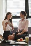 2 коммерсантки смотря цифровую таблетку, работая в офисе Стоковое Изображение