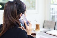 Коммерсантки советуя с партнером по телефону пока сидящ в кофейне стоковые фото