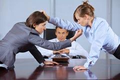 Коммерсантки споря перед бизнесменом на офисе Стоковое Изображение