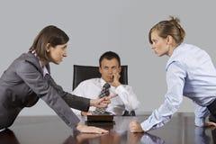 Коммерсантки споря перед бизнесменом на офисе Стоковое Фото