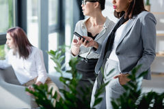 Коммерсантки стоя и используя smartphone при коллега сидя позади Стоковые Фото