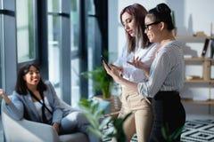 Коммерсантки стоя и используя smartphone при коллега сидя позади Стоковое Фото