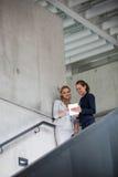 Коммерсантки стоя на лестнице и используя цифровую таблетку стоковое изображение rf