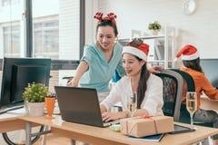 2 коммерсантки счастливой для того чтобы проверить онлайн продажу Стоковая Фотография RF