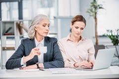 Коммерсантки с компьтер-книжкой обсуждая дело проектируют на встрече в офисе Стоковое Изображение
