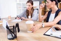 Коммерсантки с кофе на рабочем месте Стоковые Изображения