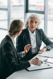 Коммерсантки с доской сзажимом для бумаги обсуждая дело проектируют на встрече в офисе Стоковое Изображение RF