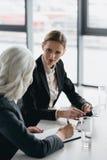 Коммерсантки с цифровой таблеткой обсуждая дело проектируют на встрече в офисе Стоковое фото RF