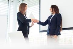2 коммерсантки трястия руки в самомоднейшем офисе Стоковые Изображения