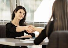 2 коммерсантки трястия руки в самомоднейшем офисе Стоковая Фотография