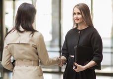 2 коммерсантки тряся руки в современном офисе Стоковое Изображение RF
