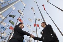 2 коммерсантки тряся руки с флагами в предпосылке. Стоковое фото RF