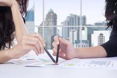 2 коммерсантки указывая на финансовую диаграмму Стоковые Фотографии RF