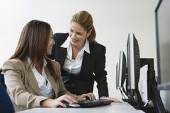 2 коммерсантки усмехаясь над компьютерами на таблице Стоковые Фото