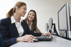 2 коммерсантки усмехаясь над компьютерами Стоковые Изображения