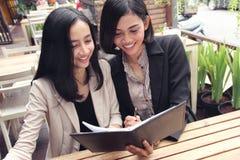 Коммерсантки читая совместно на ресторане Стоковые Изображения RF