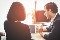 Коммерческий директор и секретарша смотря компьютер и таблетку Стоковая Фотография