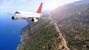 Коммерчески летание самолета над морем и береговая линия с дорогой стоковое фото rf