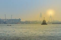 Коммерчески плавание корабля на реке около моста во время захода солнца Стоковое Изображение